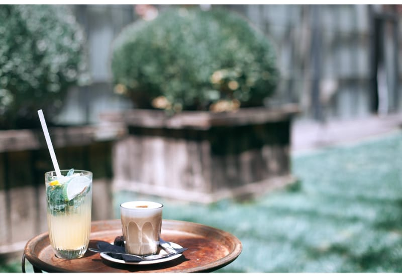 A glass of Italian soda and a glass of coffee on a round tray