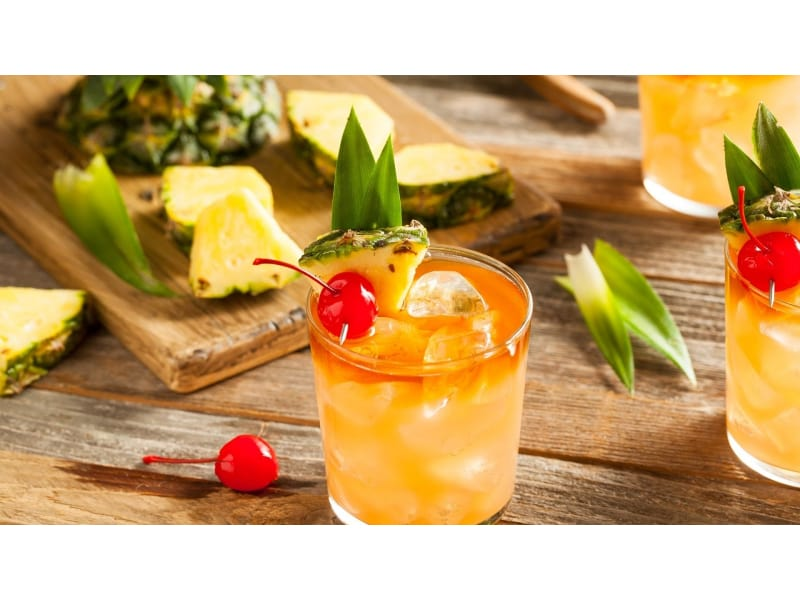 A glass of Mai Tai with fresh cherry and pineapple