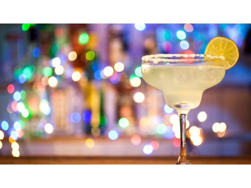 A glass of Margarita with a lemon wheel