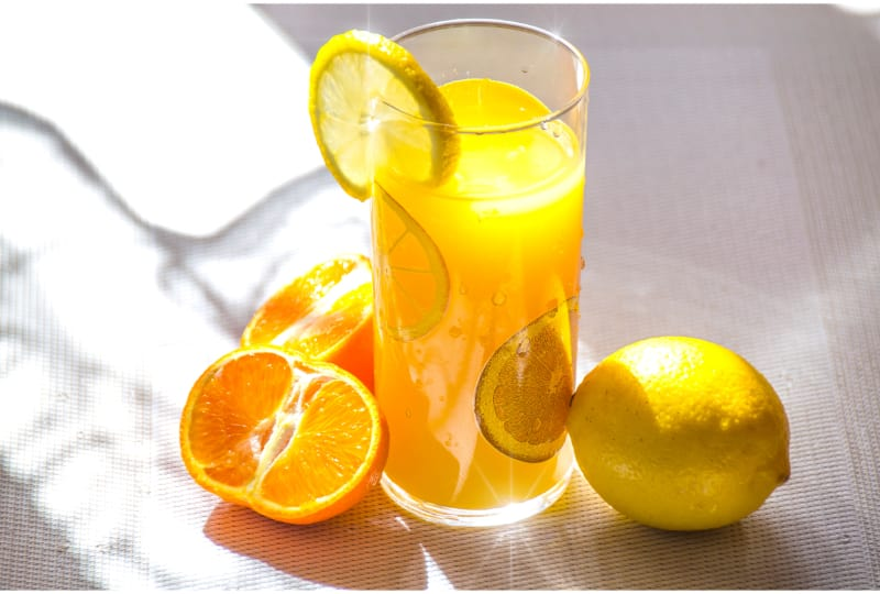 A glass of orange soda garnished with lemon and orange slices surrounded by a lemon and an open orange