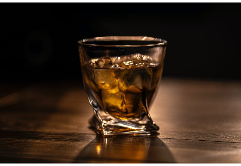 A glass of whiskey with ice