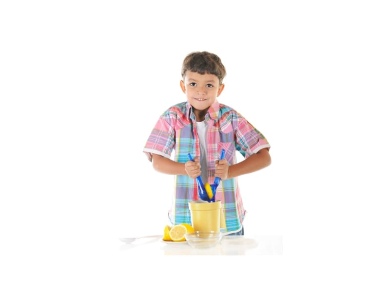 A kid squeezing lemon with a squeezer
