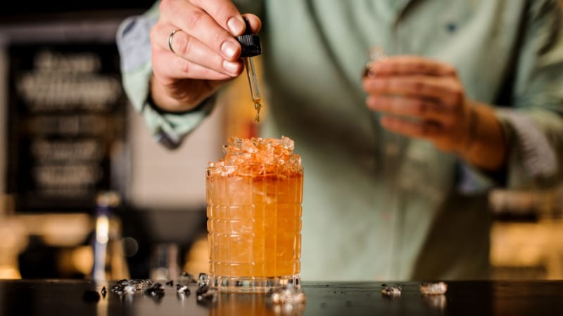 A person dropping some bitters into a cocktail