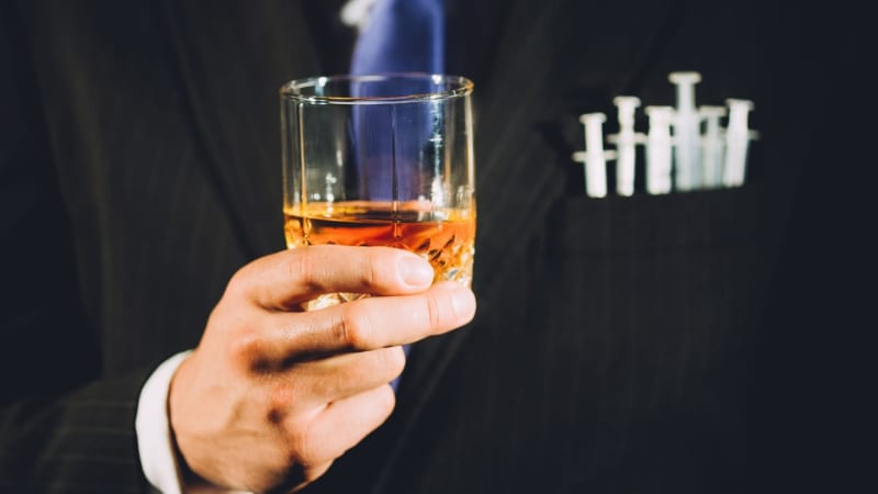 A person holding a glass of bourbon