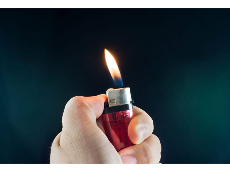 A person holding a lighter