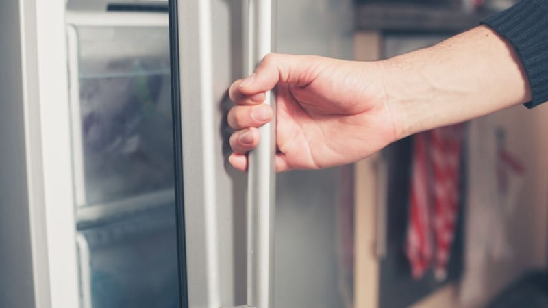 A person opening a freezer