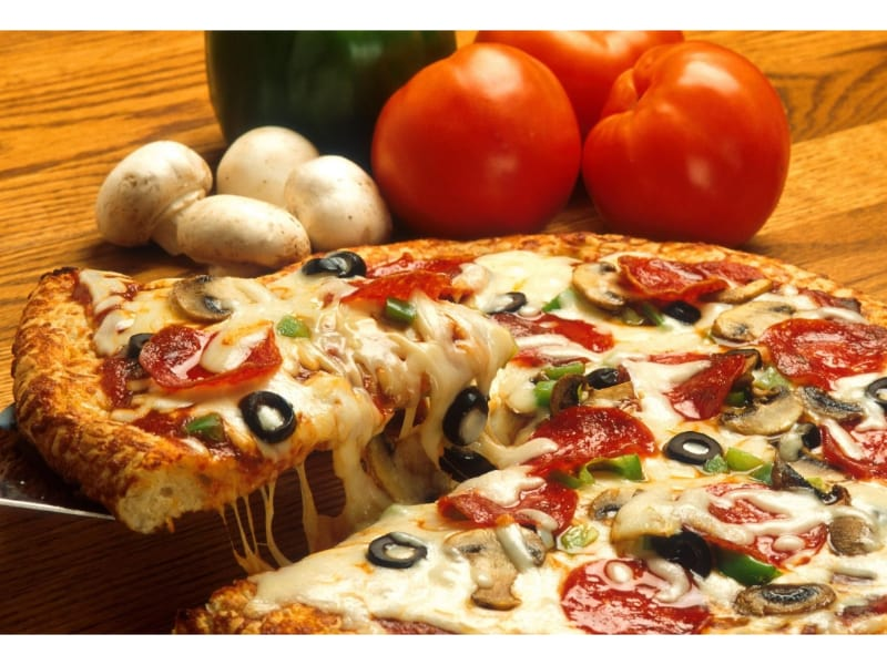 A serving of pizza with tomatoes and mushrooms