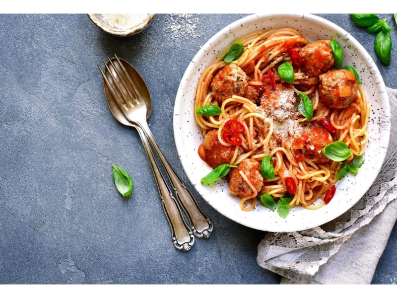 A serving of spaghetti and meatballs with utensils