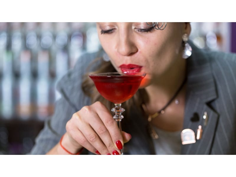 A woman sipping her cocktail