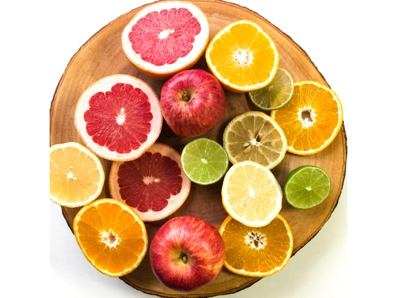 A wooden tray full of sliced citrus fruit and apples