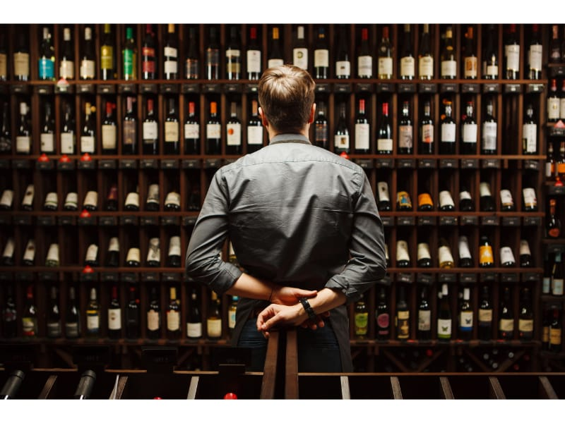 guy staring at a wine collection