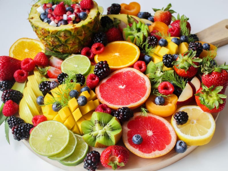 An assortment of sliced fruit on a wooden tray
