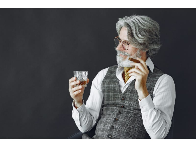 An old man holding a glass of whiskey by the base