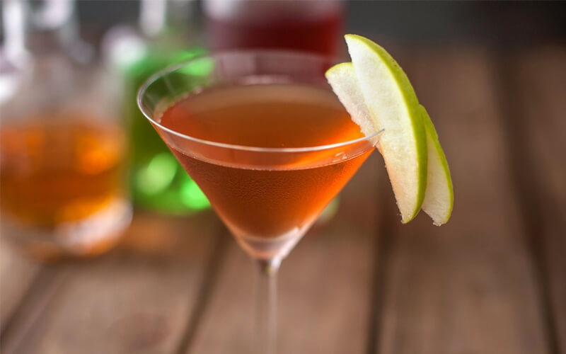 cocktail in a martini glass with apple garnish and apples in the background