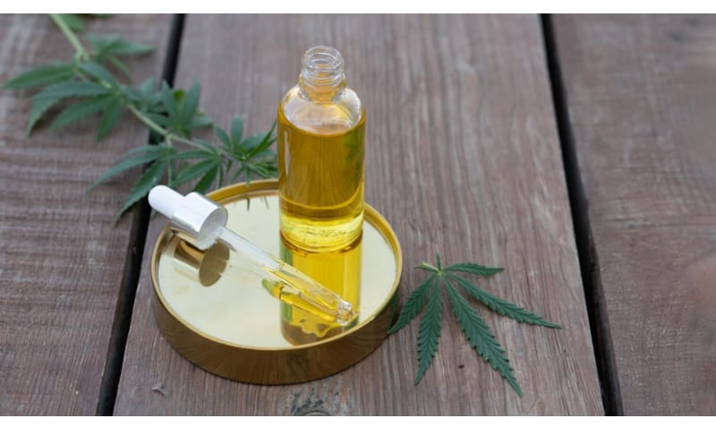 Glass Bottle Dropper of Cannabis Oil with Leaves Wooden Planks