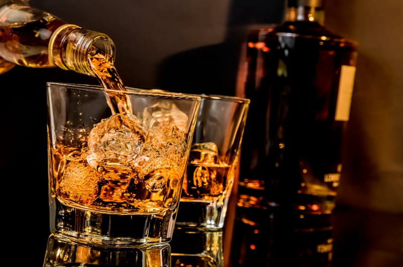 barman pouring whiskey in front of whiskey glasses and bottle