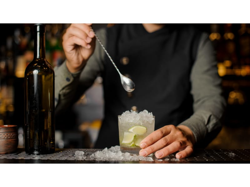 Bartender behind the counter mixing drink using bar spoon