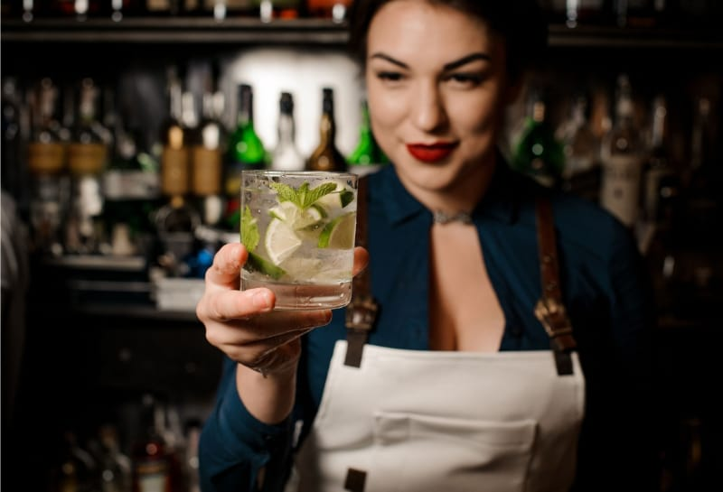 Bartender girl holding an fresh cocktail with lime and mint