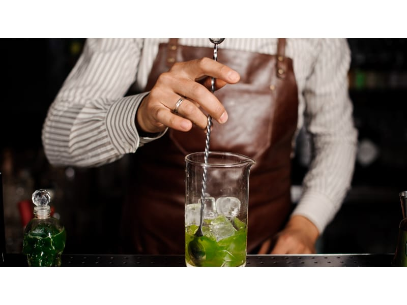 Bartender mixing cocktail using a bar spoon