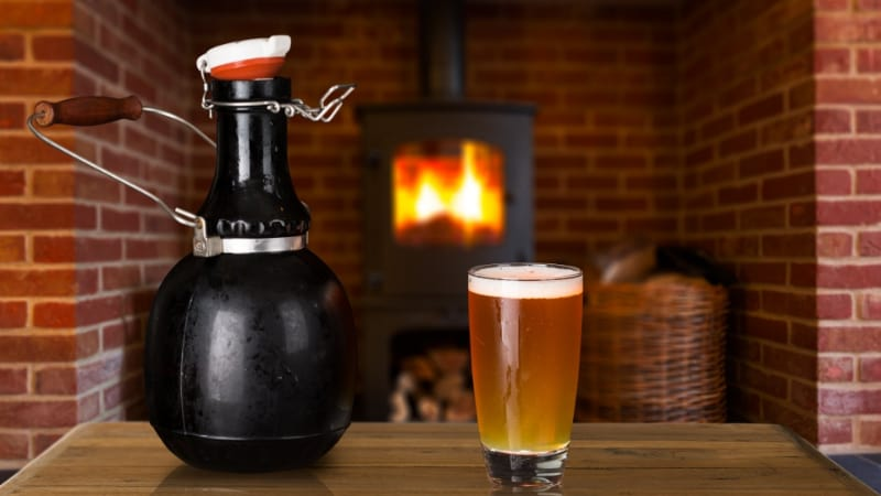 Black growler with a glass of beer