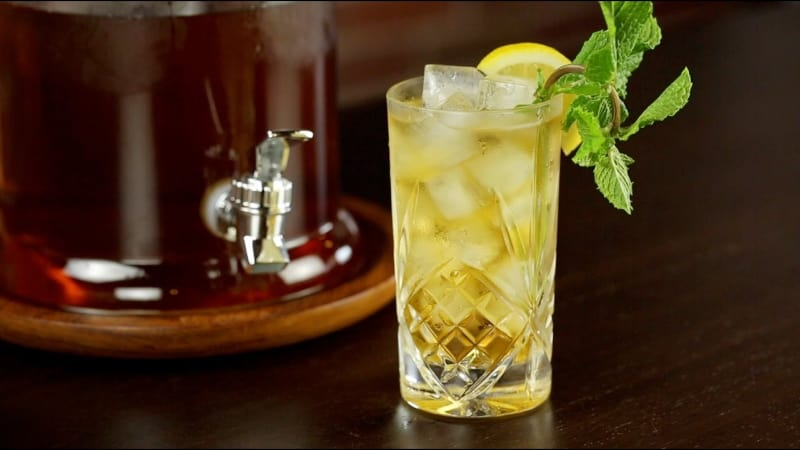 A glass of Bourbon Sweet Tea Cocktail garnished with lemon wedge and mint leaves