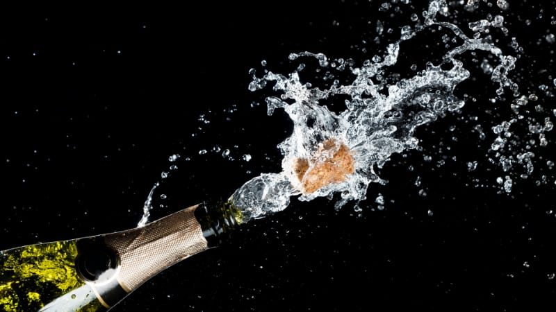 Celebration theme with an explosion of splashing champagne sparkling wine with flying cork out of the bottle