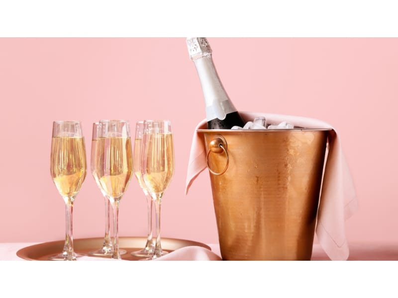 Six champagne tulip glasses and a chilled champagne bottle in an ice bucket.