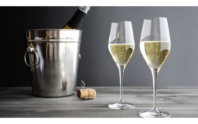 Sparkling champagne in tulip glasses with chilled champagne in a bucket on the side.