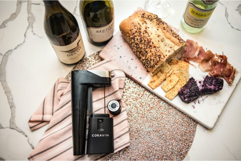 Coravin wine preservation system on a marble counter with bottles and charcuterie board