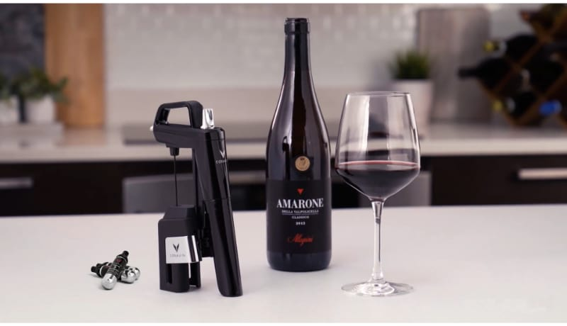Coravin wine preservation system with wine bottle and wine glass on the table