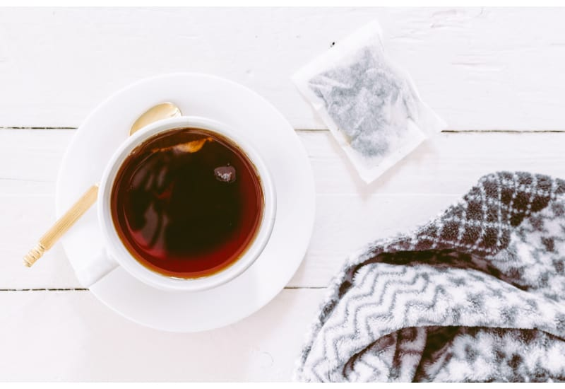 Cup of tea with a teabag on a wooden table