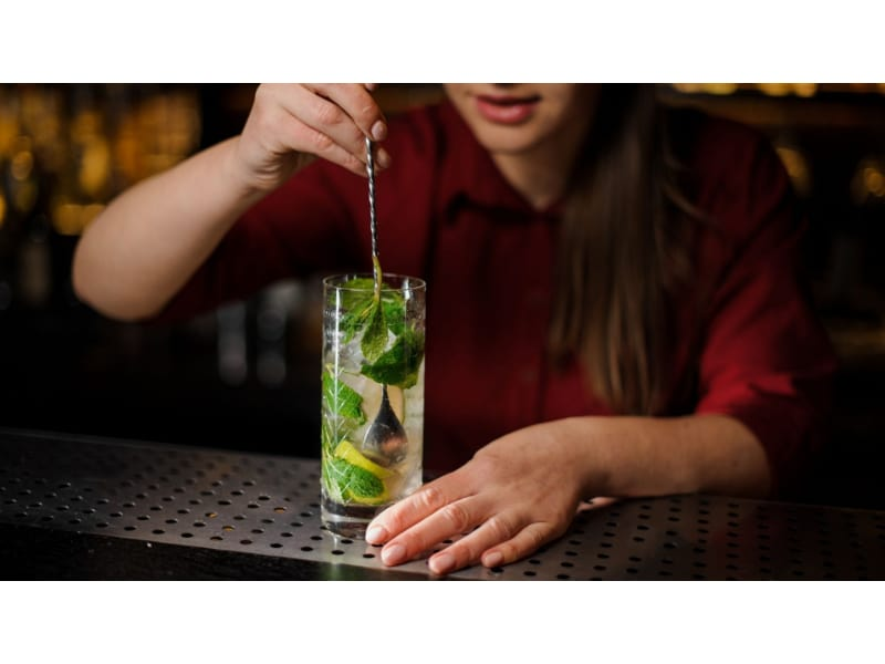 Female bartender mixing cocktail with a bar spoon