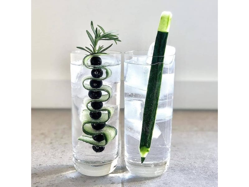 Glasses of G&T cocktail with a cucumber garnish