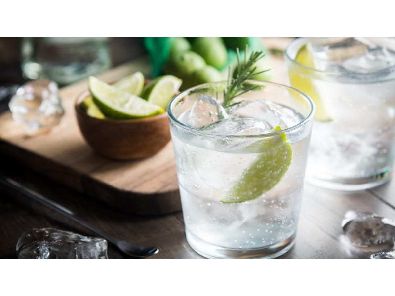 Gin cocktail with a bowl of lime slices