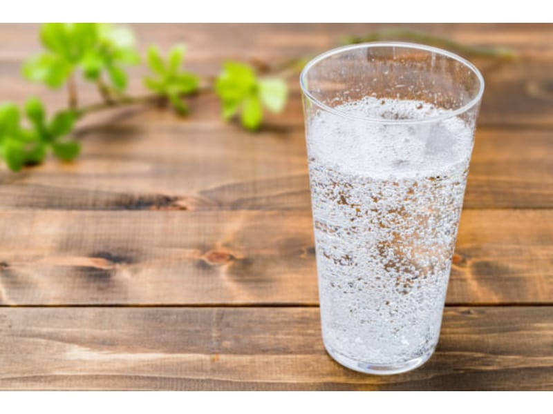 Glass of carbonated water on a wooden surface