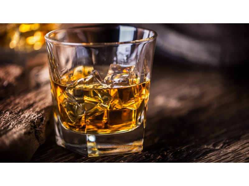 Glass of whiskey on a wooden surface