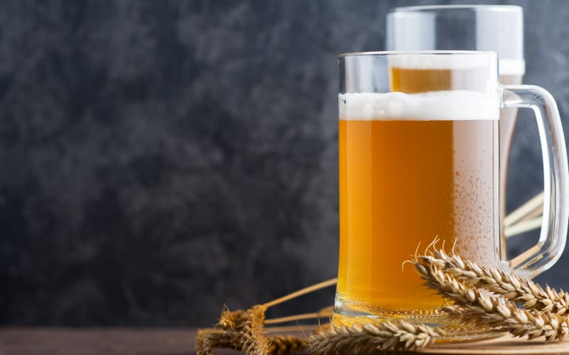 Glasses of Beer and Wheat Ears on a Table