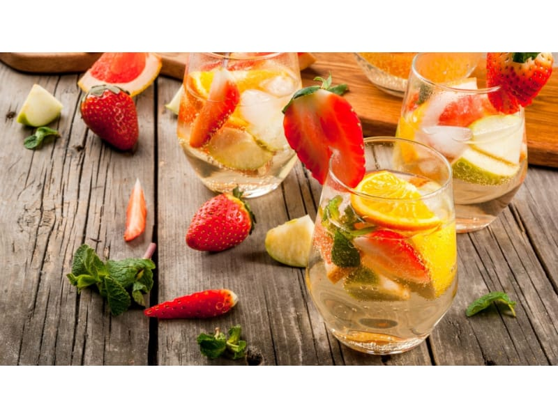 Glasses of Sparkling Green Sangria with strawberries and oranges