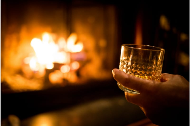 Hand holding whiskey glass at the fireplace