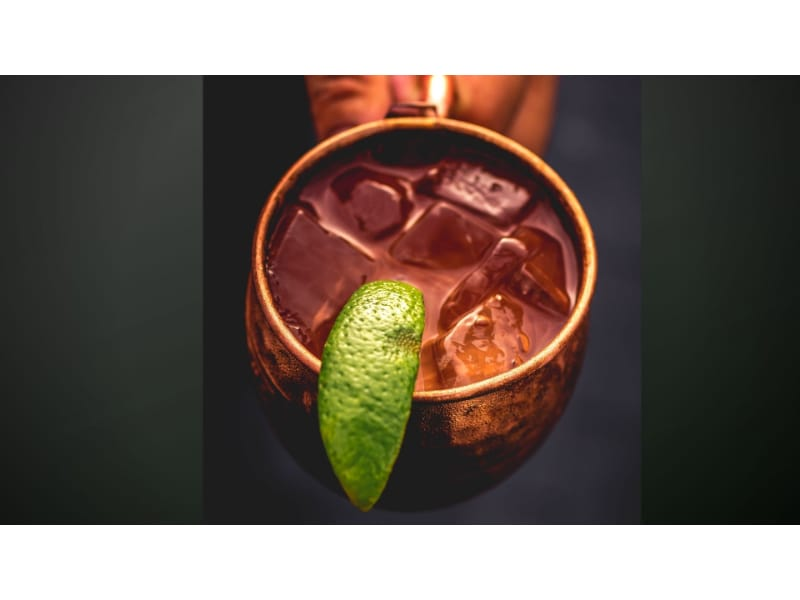 Holding a moscow mule cup of Dark N Stormy drink