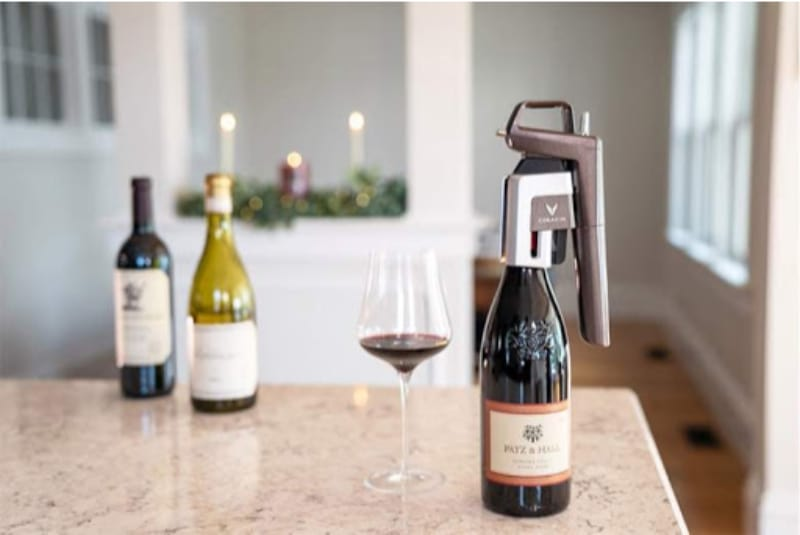 3 bottles of wine, one with Coravin system attached, and a wine glass filled with red wine
