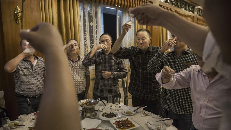 Chinese people toasting and drinking Baijiu - Image by CGTN
