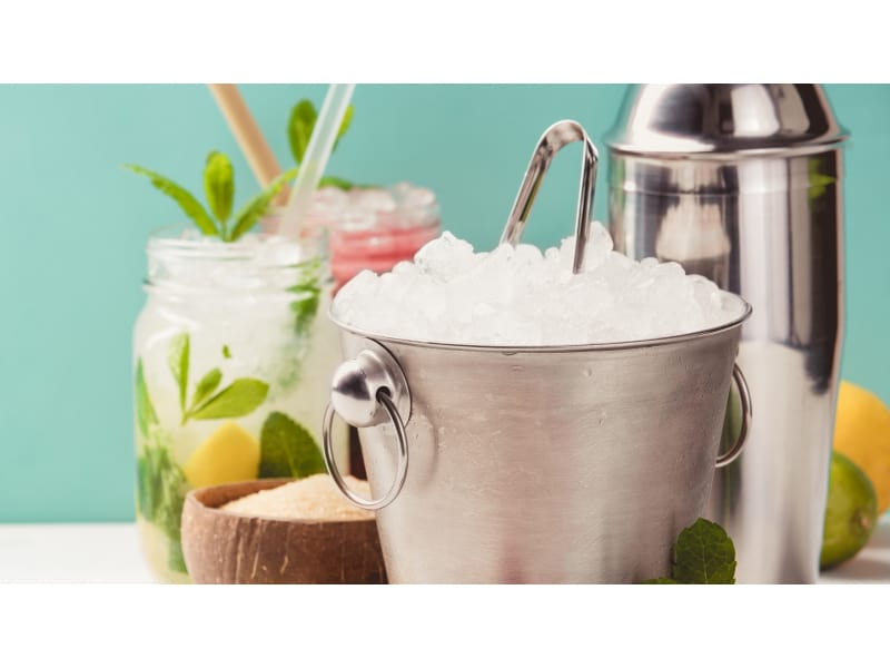 Ice bucket full of ice with tongs on top surrounded by a cocktail shaker and mason jars