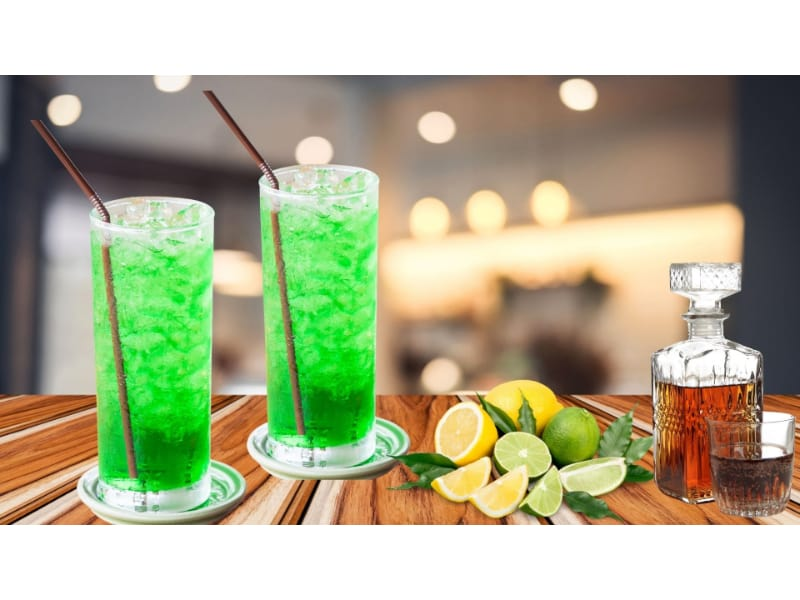 Incredible Hulk with lime and lemon soda served in two highball glasses with lemon and lime and cognac on the side