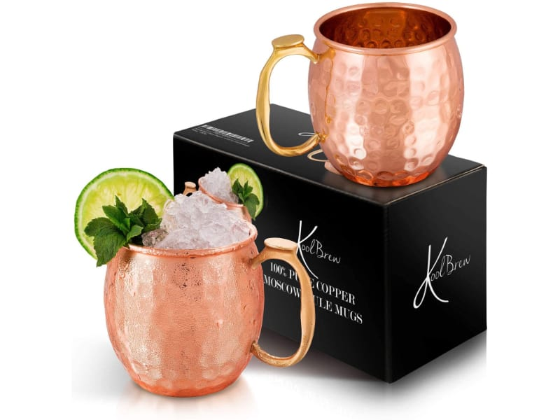 2 KoolBrew copper mugs filled with liquor, lime on the side, and a gift box