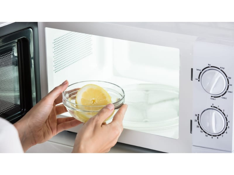 Lemon being placed inside a microwave