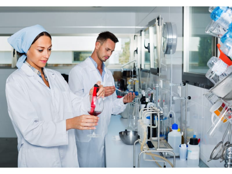 Chemists in a laboratory testing red wine