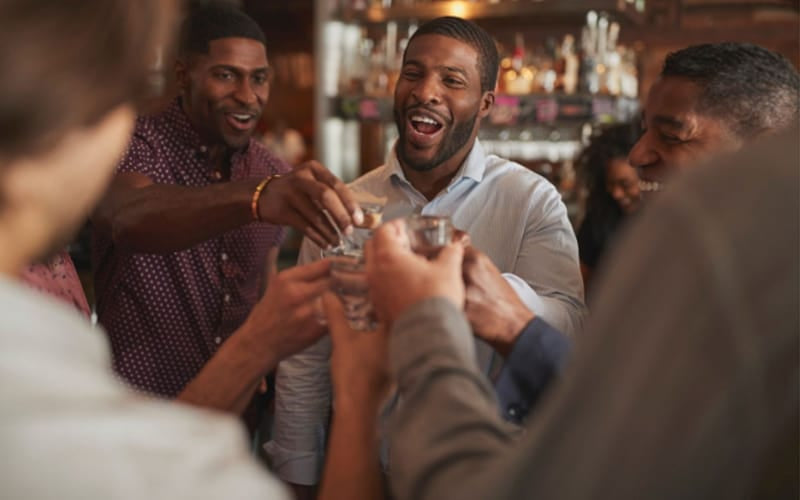 Male Friends on Night Out Drinking Shots in Bar Together