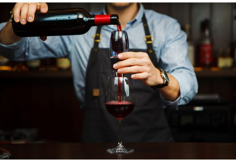 Male sommelier pouring red wine through aerator into glass