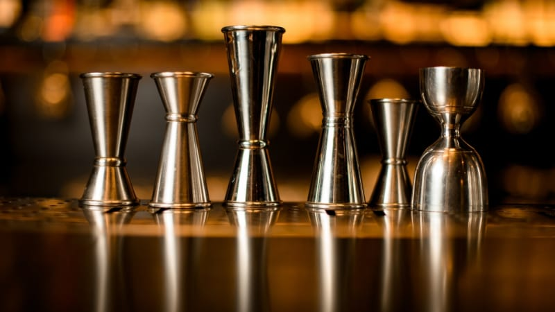 Many different jiggers stands in row on the bar counter